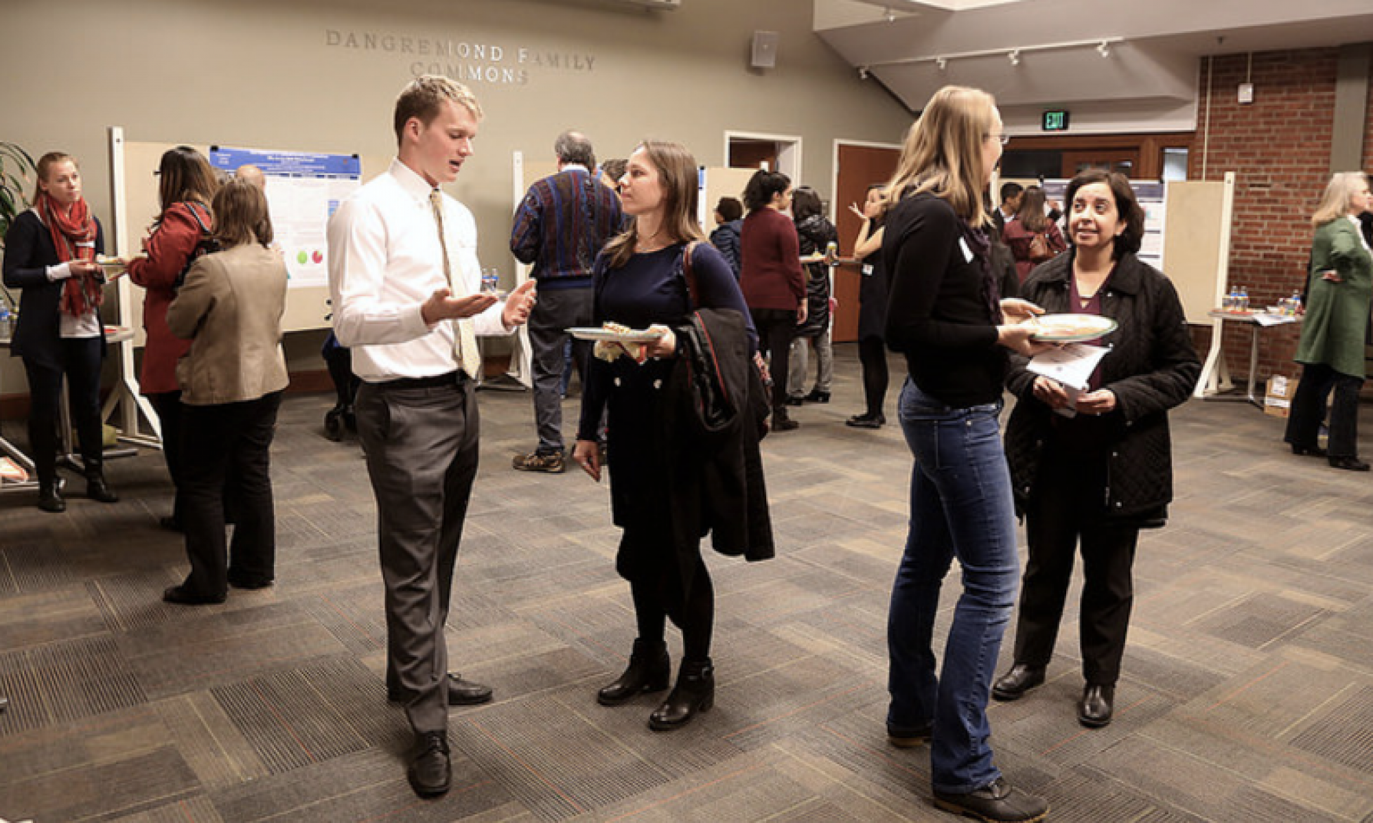 Students and Faculty converse during a research poster session