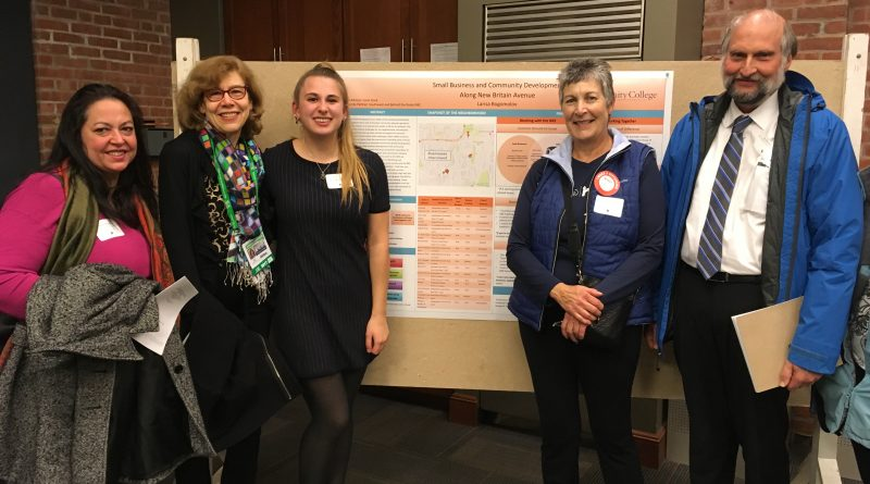 At the Research Fellows presentations, Larisa Bogomolov '20 stands in front of her poster with Professor Janet Bauer and her community partners from the South West/Behind the Rocks Neighborhood Revitalization Zone