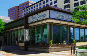 Trinity's 10 Constitution Plaza building in downtown Hartford. This one-story, glass building is above street level surrounded by other downtown businesses.