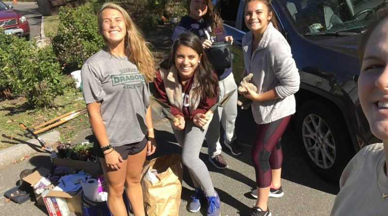 Four trinity students pose with shovels as they prepare to weed out invasive species from a local riverfront