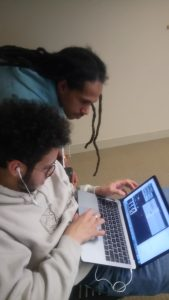 Khaiim Kelly instructs Cody Maldonado on how to use beat making software.