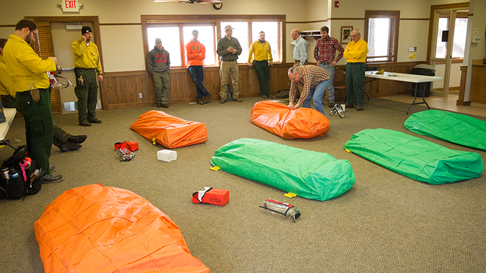 Yep, that's us under our practice fire shelters. The real thing is made of some space-age fiberglass-aluminum composite, weighs a ton and costs even more. We were only allowed to play with the practice version.