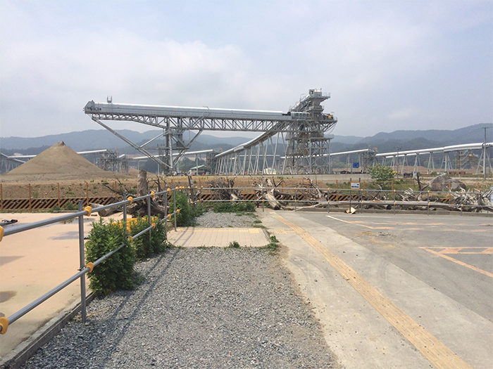 Conveyors bringing earth materials from mountains in the background.