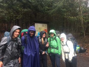 Students in ponchos out on a trail for Quest training