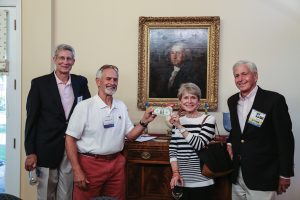 Ed Landes '66, David Sample '71, P'06, '09, '15, Nancy Landes, and George Andrews '66 compare the artwork of American artist Gilbert Stuart, featured on the $1 bill, with a painting at the President's House.