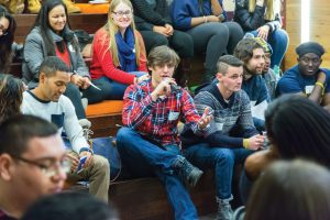 Davis United World Scholar Timothy McDermott '18, with microphone, voices his thoughts at the leadership summit.