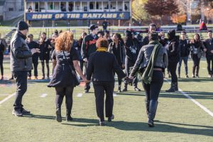 President Joanne Berger-Sweeney, center, and two students walk hand in hand at a demonstration of solidarity at Homecoming 2015.