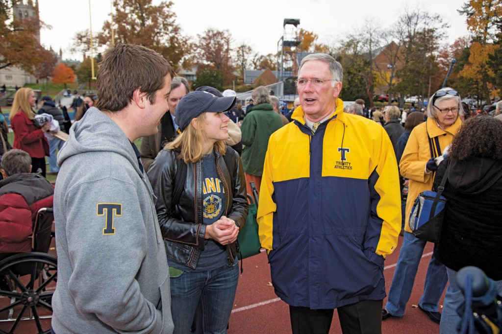 Jones speaks with Elizabeth Gerber '14 and Benjamin Rudy '13 during the 2013 Homecoming football game. Jones's wife, Jan, is at right.