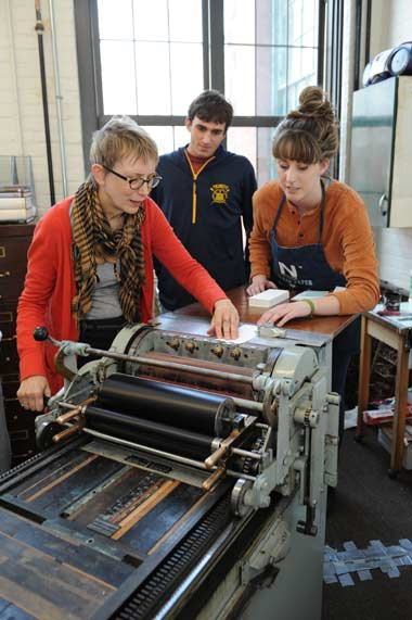 Aidan Willner '17, center, watches as Trinity Artist-in-Residence Clare Rossini works with Kaitlin Lennon of Hartford Prints!, a local letterpress shop.