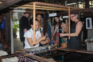 Stern Family Scholar Crystal Rosa '14, second from left, and Class of 1916 Scholar Kaitlyn Sprague '16, second from right, listen as Carol Cassidy, right, owner of Lao Textiles in Vientiane, Laos, describes the work of the weaver at left.