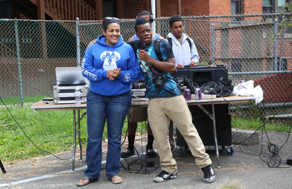Olivia Berry '14, Posse Scholar Nijel Hill '15, Lucy M. Brainerd Memorial Scholar David Johnston '16, and Jordan Green '13 (behind Hill) entertain the crowd at Trinfo.Café's sixth annual Back to School Community Barbecue in September 2013.