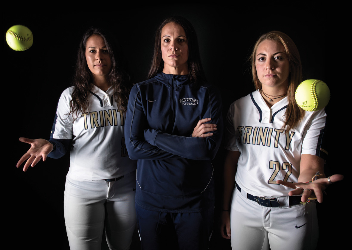 Two softball players and their coach