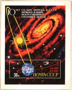 Postage stamp shows Earth in orbit around Sun with a man-made object in Earth orbit.