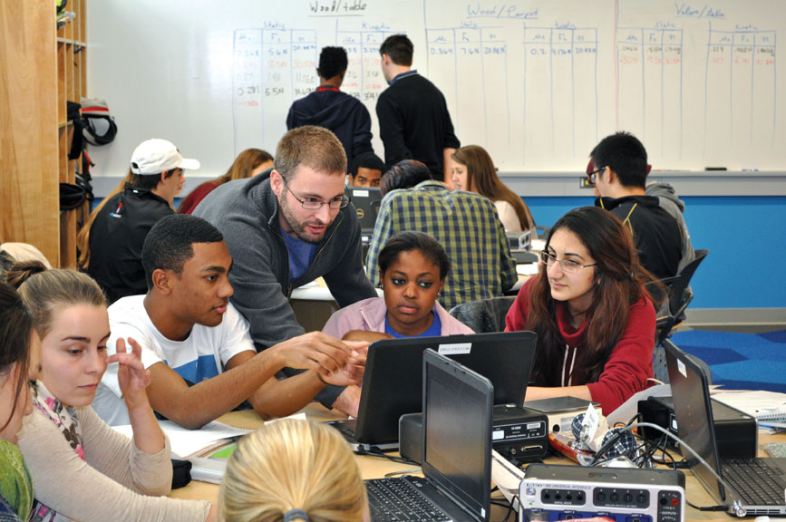 Assistant Professor of Physics Brett Barwick works with students in Physics 141.