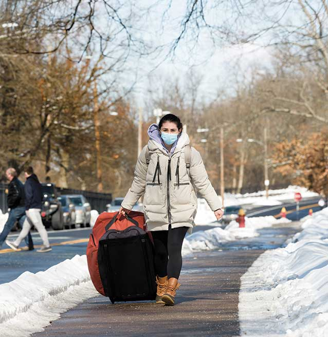 student walking with suitcases